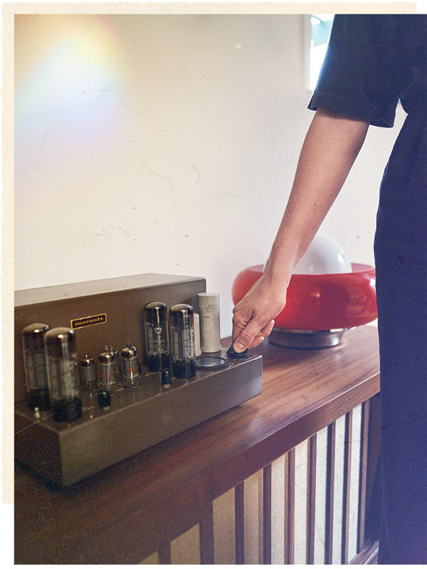 Alana turns a knob on the Marantz Model 8 amplifier.