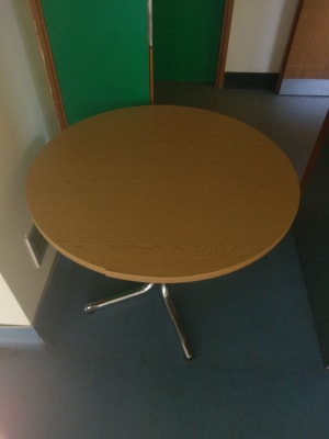 round gray metal based brown wooden table