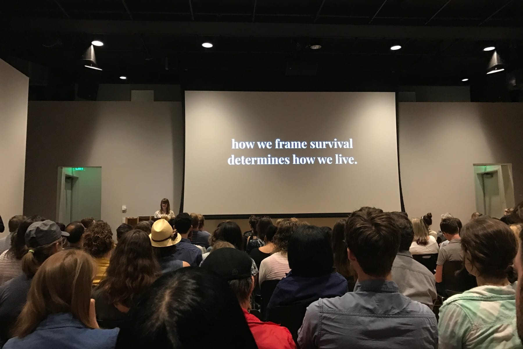 Traci Sym speaking in front of an audience at Creative Mornings PDX - How we frame survival determines how we live
