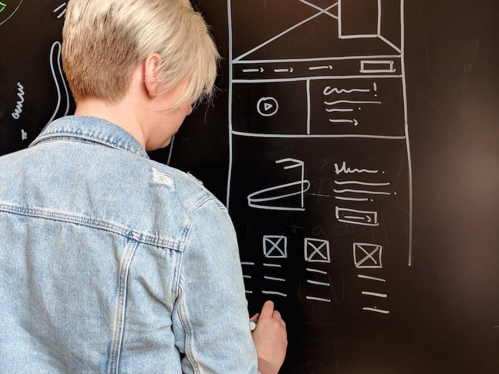 Lacie Webb drawing wireframes on a chalkboard