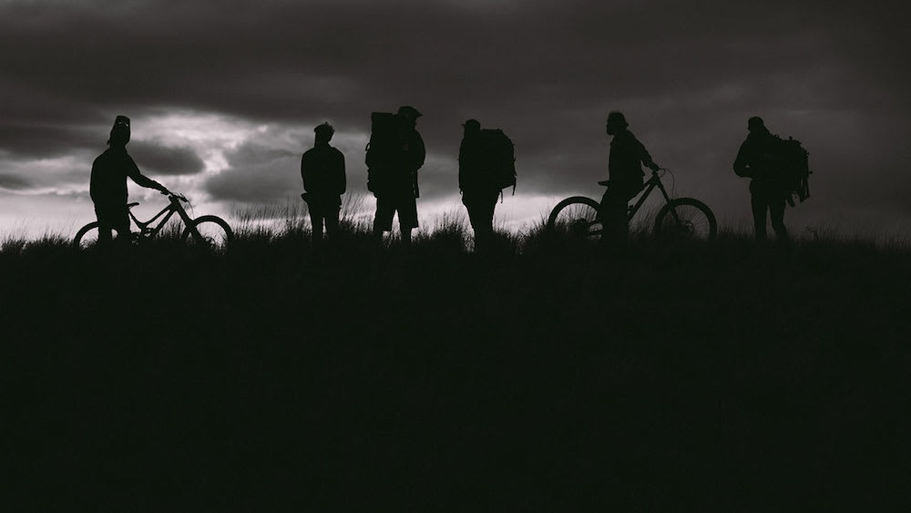 Silhouette of riders with bikes and sunset in background