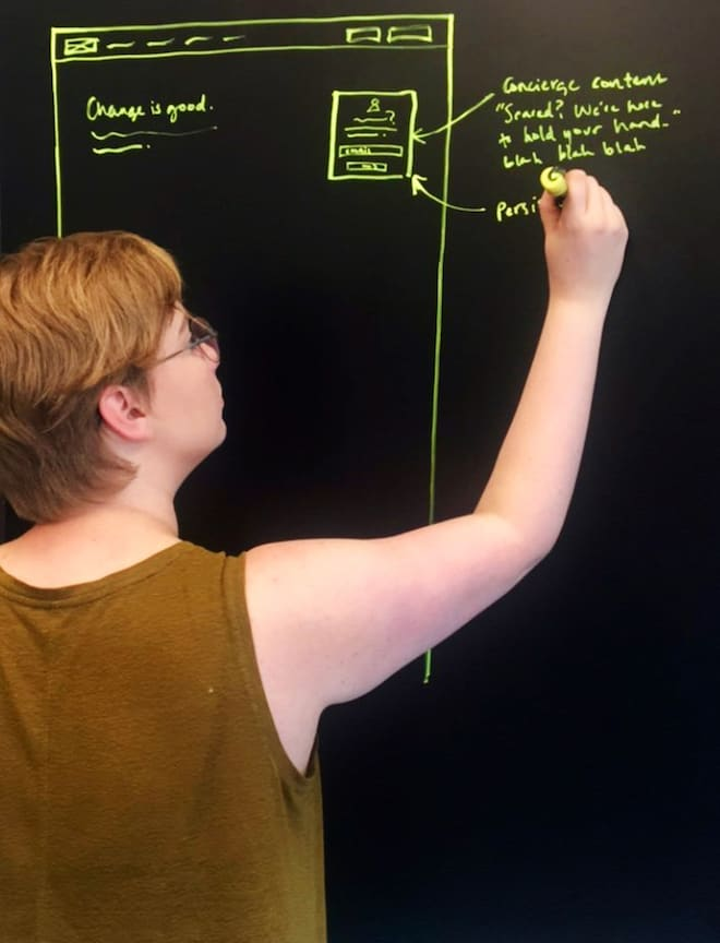 Lacie Webb drawing wireframes on a blackboard