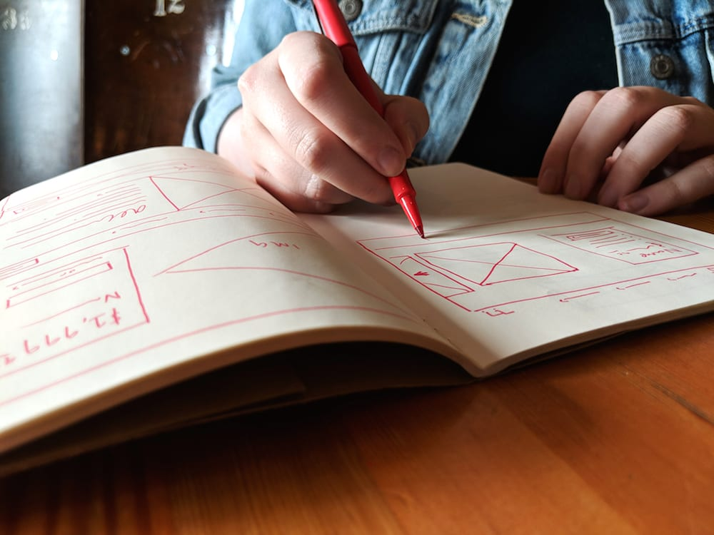 Lacie Webb draws wireframes in a notebook