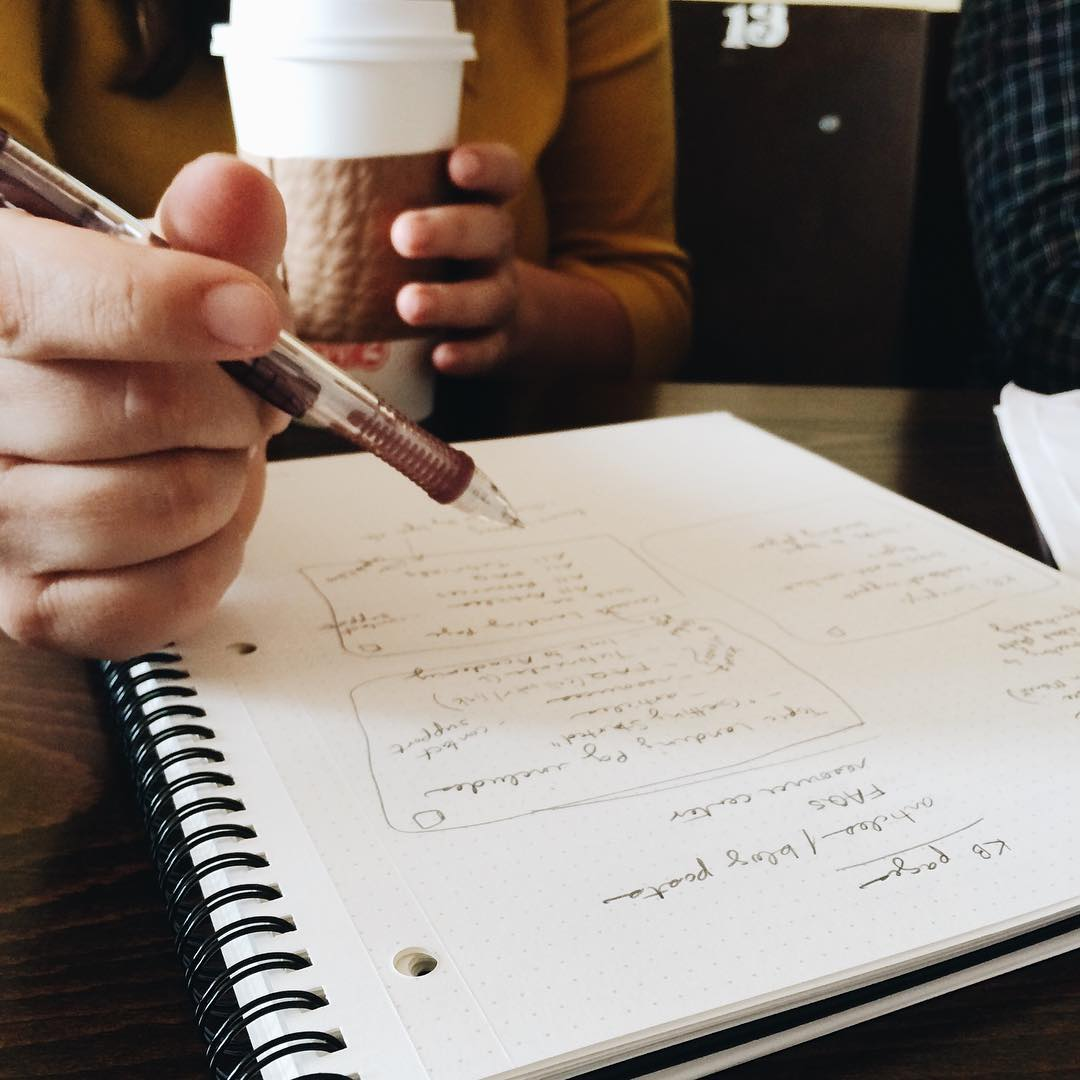 member of team roboboogie taking notes in notebook and drinking coffee
