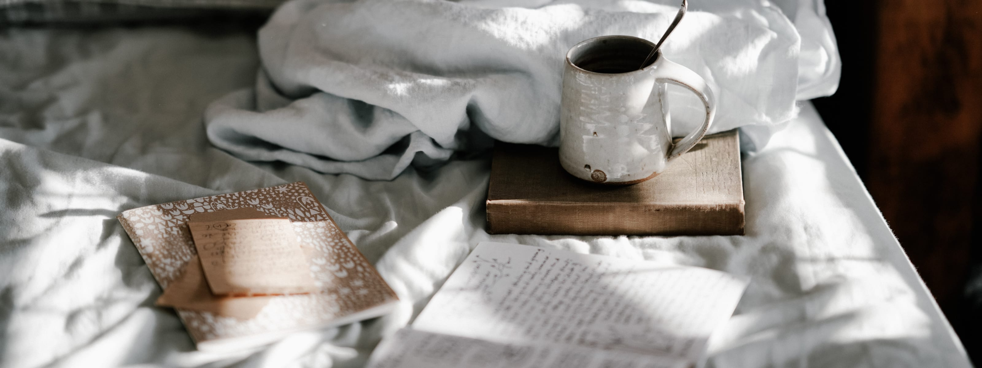 Coffee, journal, and bedsheets