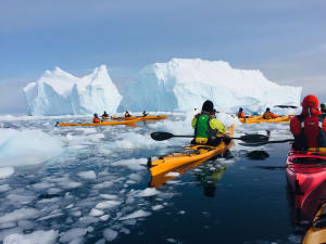 Group of kayakers moving past an iceberg, ice in the water around them