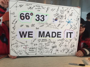 "Poster saying ""66 degress 33 minutes - We Made It"" signed by all the travellers"