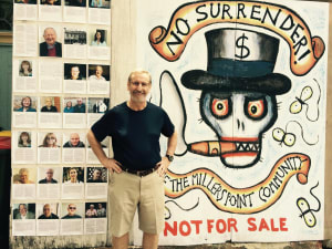Dr Michael Kendrick in front of the large 'No Surrender' artwork by Margaret and John, original by Reg Mombassa