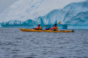 Two kayakers, iceberg in the background