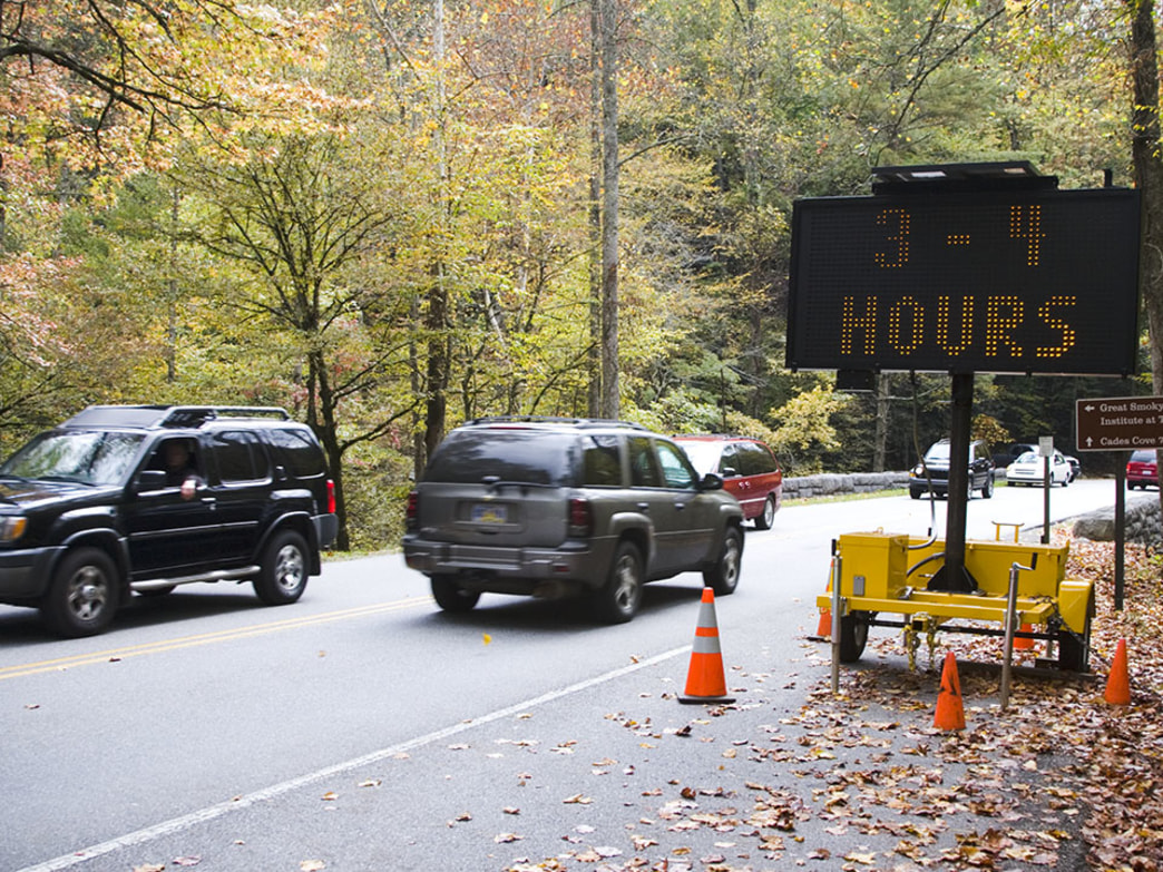 Cars pass a three to four-hour warning while entering Cades Cove in The Great Smoky Mountains National Park.