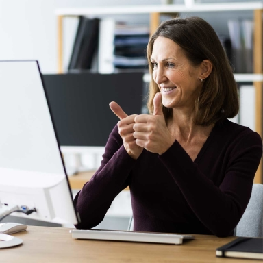 female smiling and looking at a computer monitor, with two thumbs up