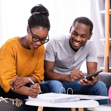 young woman and man sitting, smiling and looking over paperwork with a calculator
