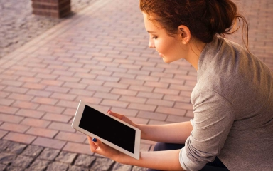 young female sitting and reading content on a tablet