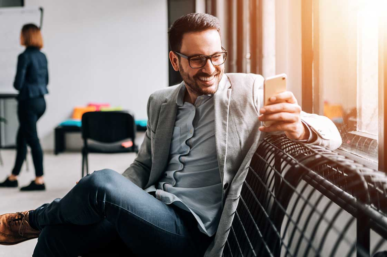 man with glasses wearing sport coat sitting on bench smiling and looking at mobile phone