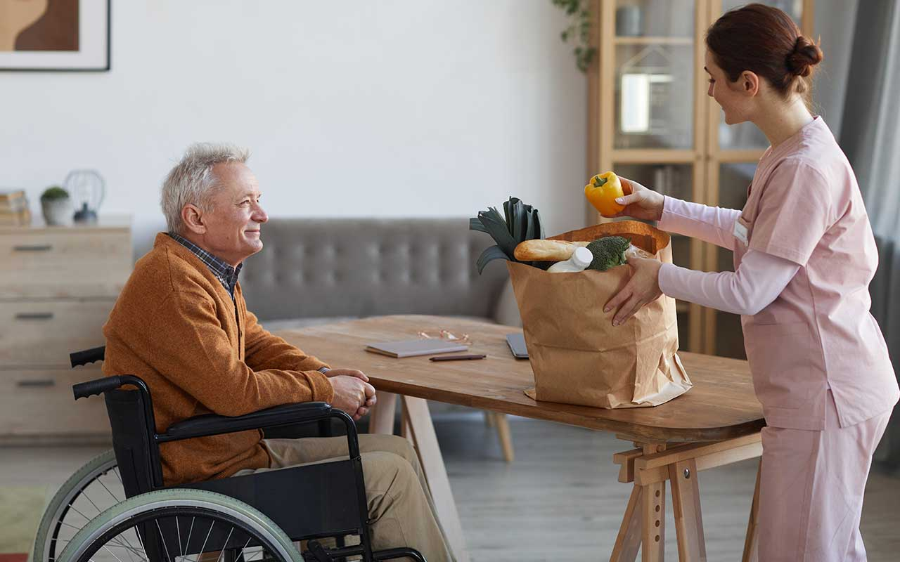 A man in a wheelchair sitting at a table while a caretaker holds a bag of groceries.