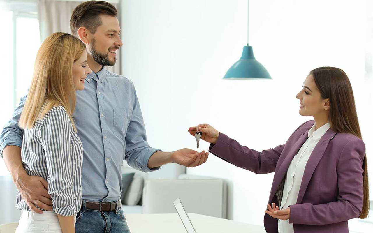 A real estate agent who is handing keys to a house keys over to a couple