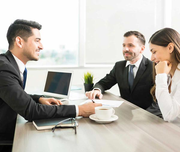 A real estate agent who is going over paperwork with a couple