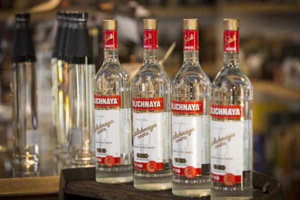 Vier Stolichnaya Vodka Flaschen auf Theke aufgereiht
