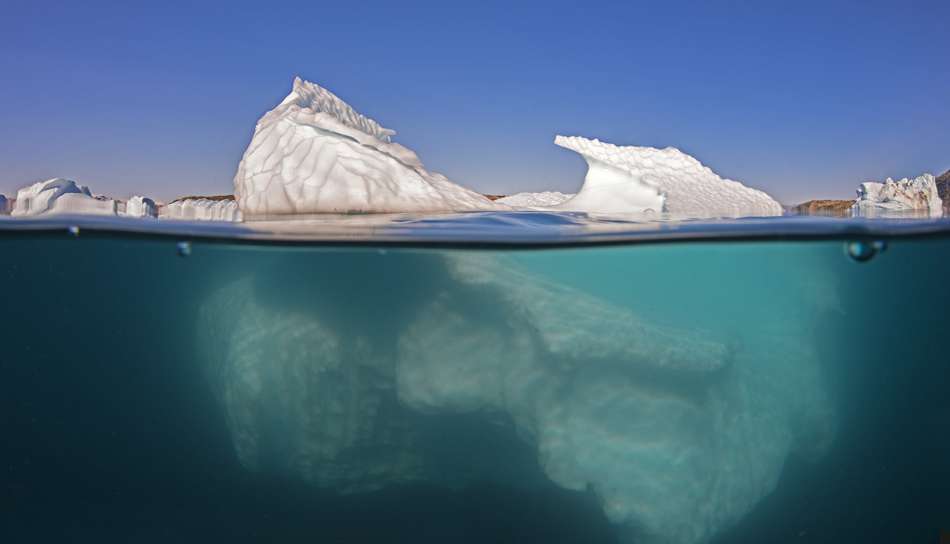 In Greenland, the only thing larger than whales are icebergs. Until you get in the water, you do not understand just how big they are, says Dhritiman. Above the water, the icebergs are hard, sharp, and sculpted, but viewed from underwater they take on a softness and otherworldly quality.
