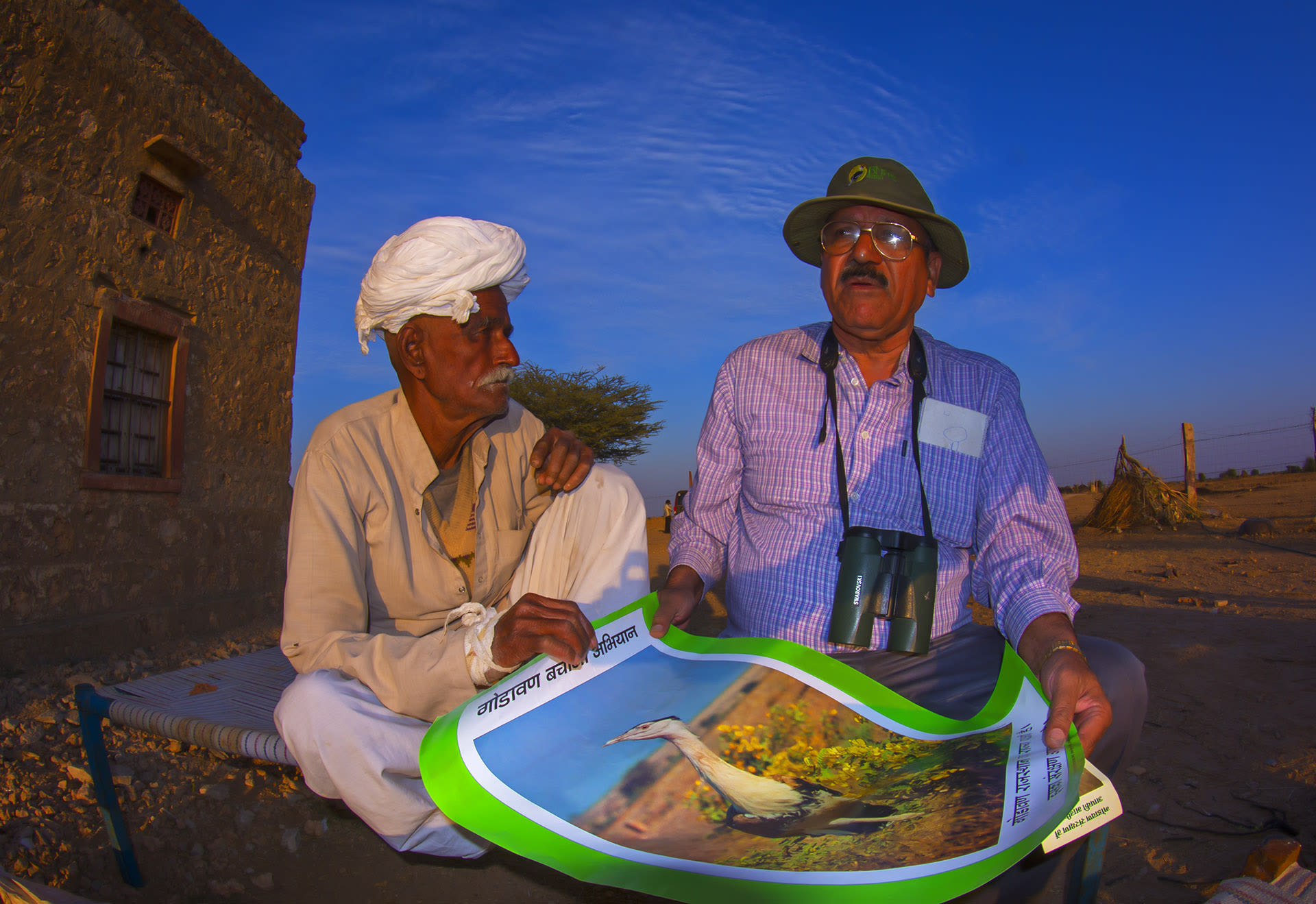 Asad Rahmani's work often involves engaging with local communities. Here he speaks about the need for conservation of the great Indian bustard to a local in Rajasthan. Photo: Dhritiman Mukherjee