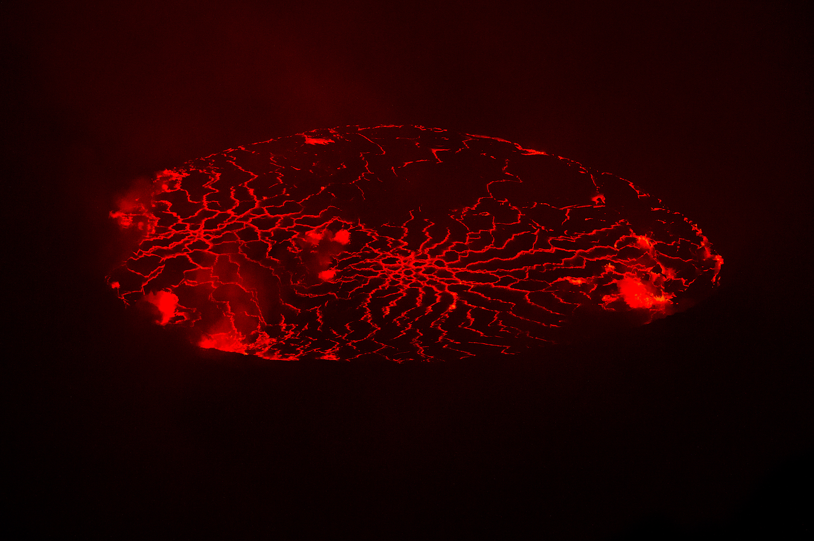As night falls, Nyiragongo reveals its true colours. I set up my photographic equipment for an all-night vigil of the volcano. The best way to see it is in the dark, when the glowing red molten lava, and the cracks and fissures stand out.