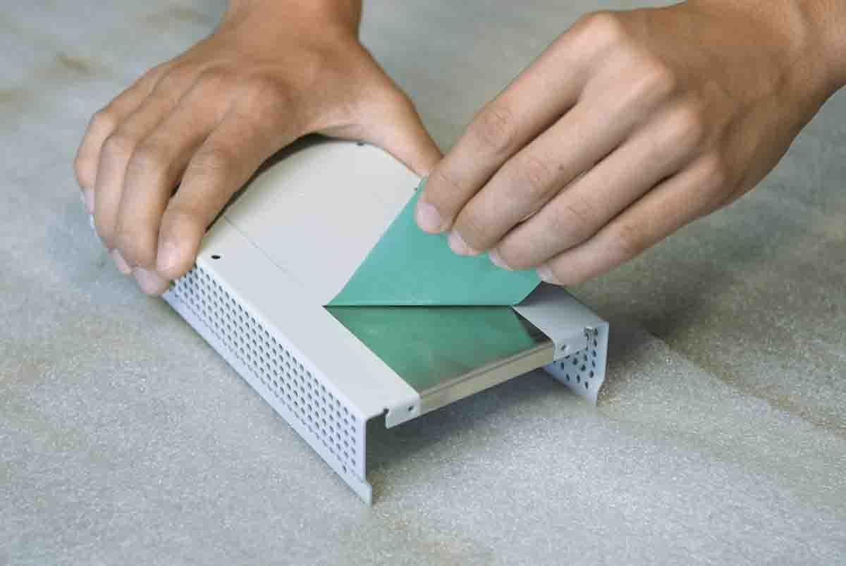 Hände, die einen Streifen Abdeckband von einer lackierten Oberfläche abziehen