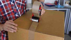 Ein Paket, das mit Hilfe eines Klebebandrollers verklebt wird