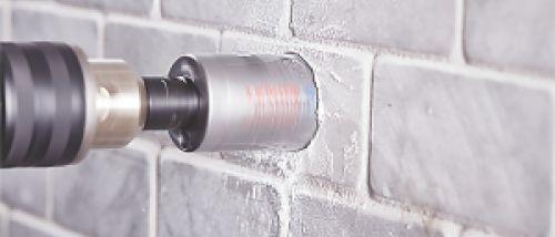 Bild einer Bohrmaschine mit Lochsäge, die in ein Mauerwerk fräst