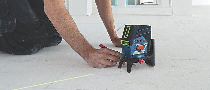 Ein Bauarbeiter benutzt ein Laser-Nivelliergerät am Boden