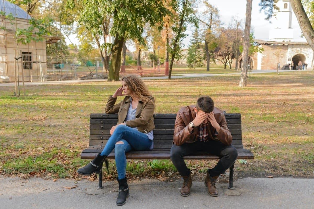 couple sitting on park bench having argument
