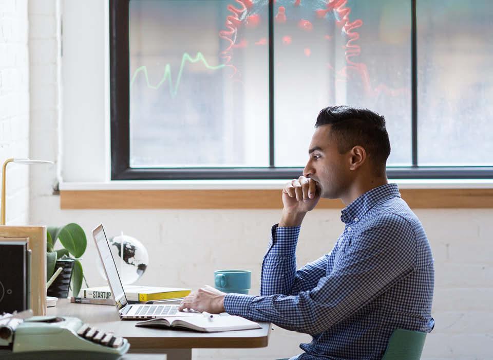 man sitting at desk looking at a computer
