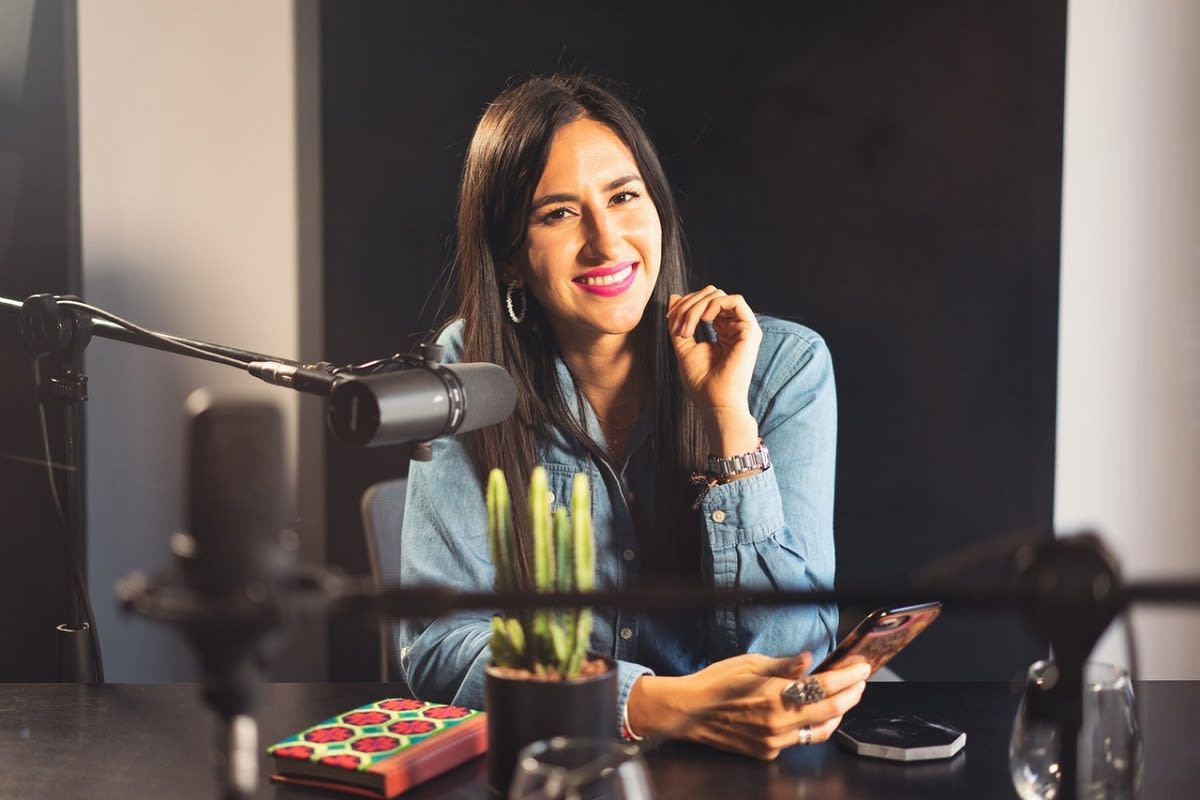 woman in front a podcasting mic