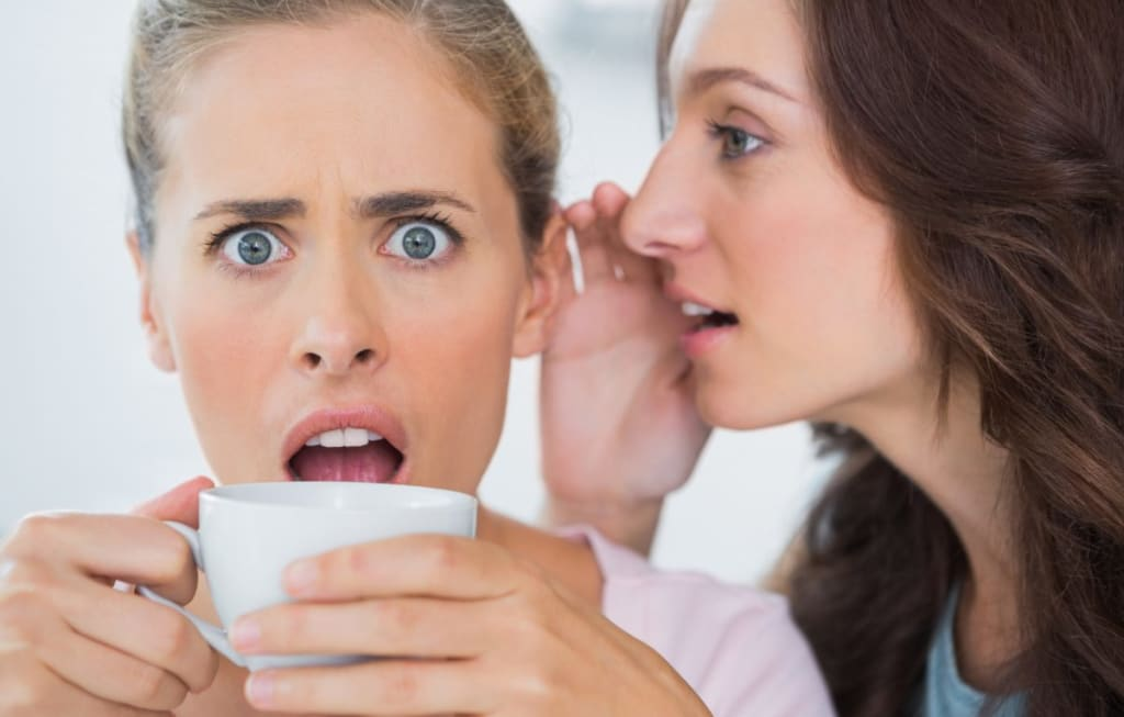 Woman telling secret to her friend and astonishing her while drinking coffee