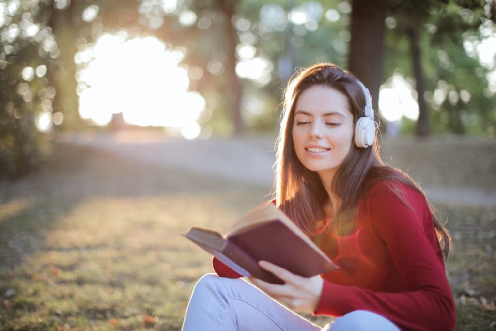 girl reading a book listening to headphones