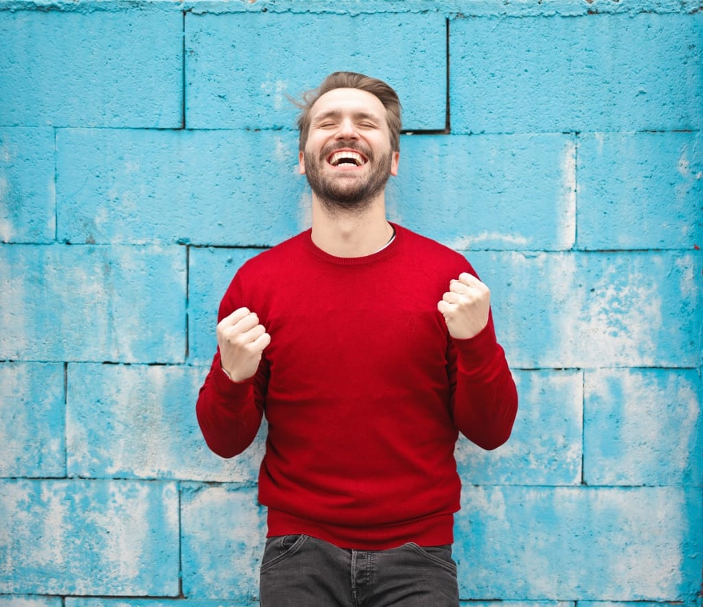 happy man in front of blue wall