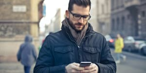 Podcast Needs An Email List Man Holding Smartphone