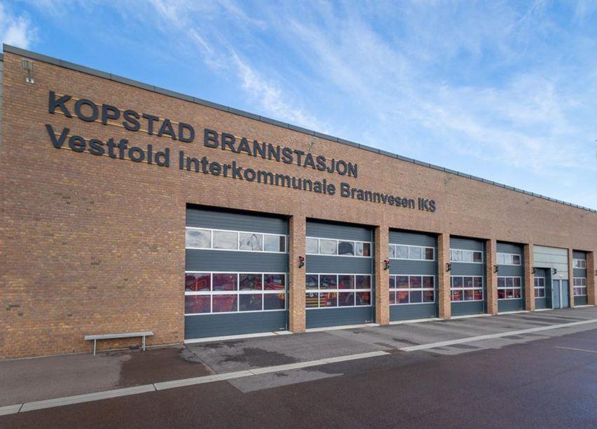 Et brunt murbygg med fem garasjeporter, Kopstad Brannstasjon.