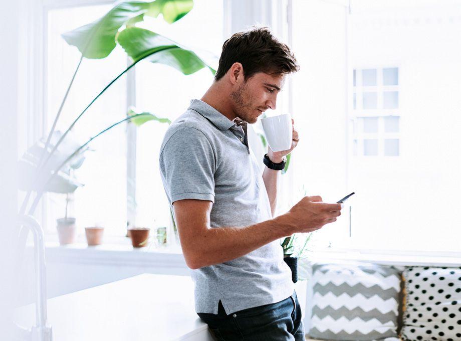 man drikker kaffe og ser på telefon - smarthus juseringer