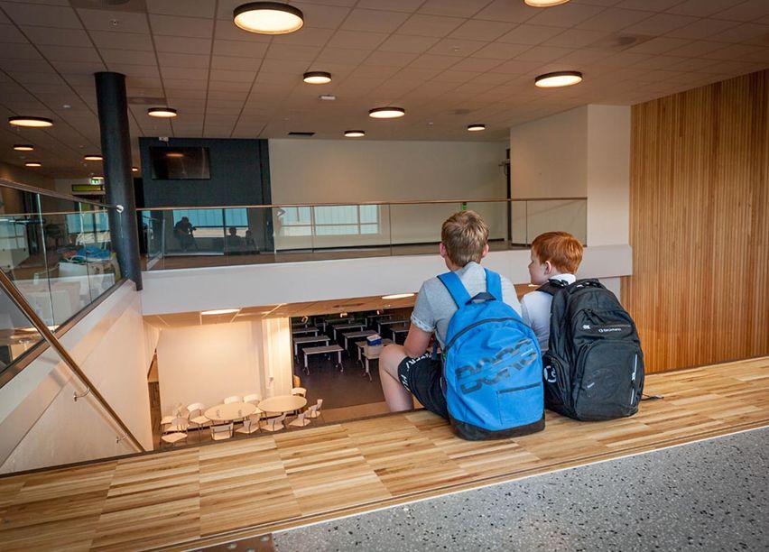 To gutter sitter med ryggen til, begge har ryggsekker på, de sitter inne på en ungdomskole.