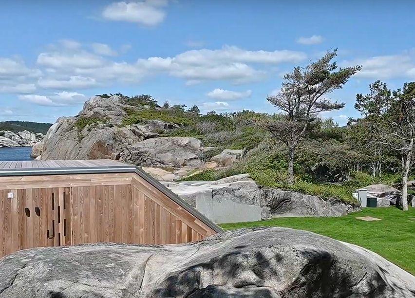 Enebolig i funkis stil, ved vannkanten i Sandefjord, omringet av berg og trær.