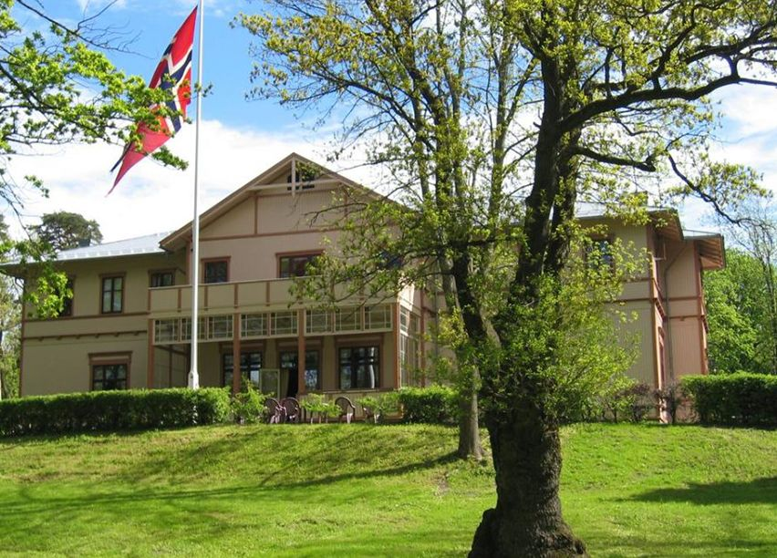 Bilde av en stor herskapelig bygning i tre, med flaggstang og store trær på utsiden.