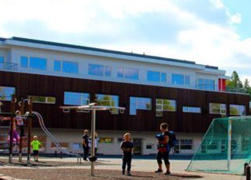 Barn leker på en lekeplass utenfor en skole.