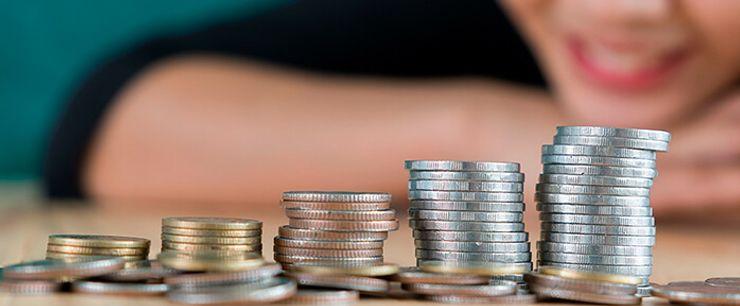 kvinne som smiler foran stabler med penger