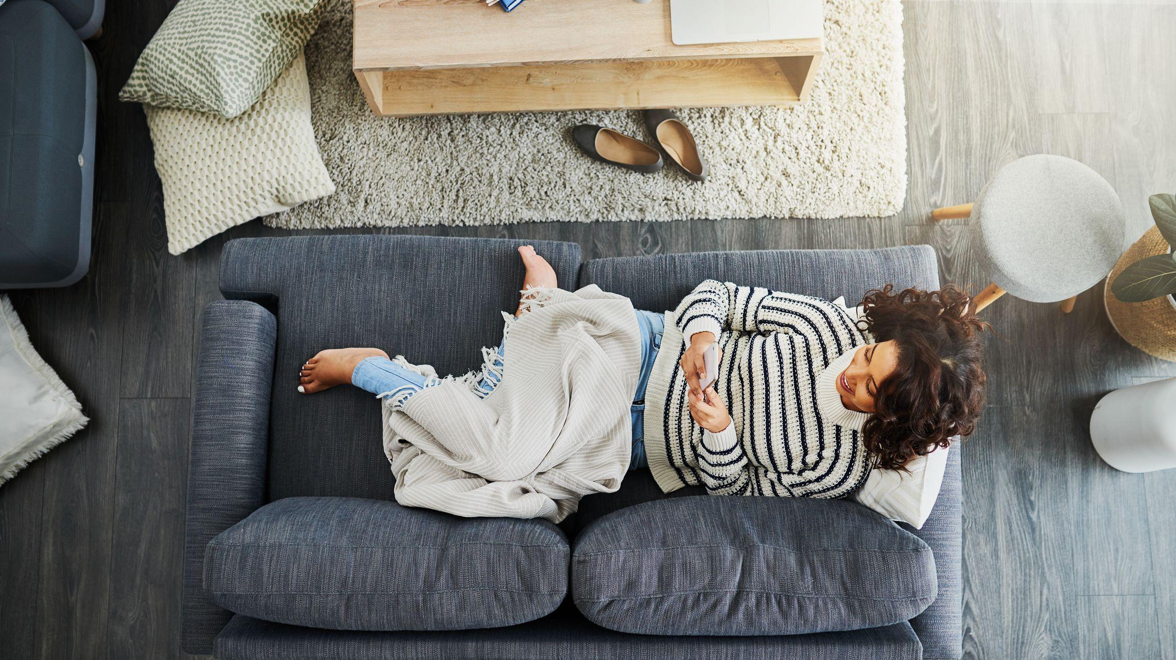 kvinne i sofa med mobil