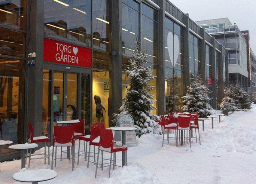 Bilde av et bygg, over inngangsdøren henger et rødt skilt der det står Torg gården, utenfor er det mange rød stoler og bord.