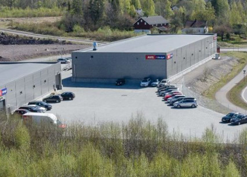 Stort grått næringsbygg, med mange parkeringsplasser.