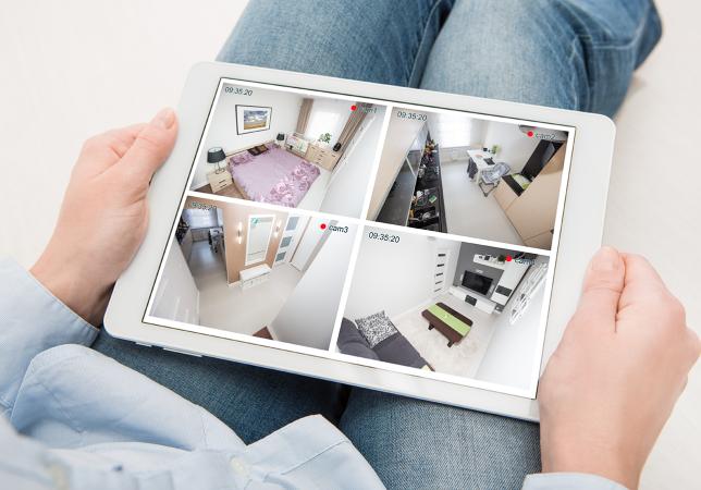 Kvinne ser på videoovervåkning i smarthuset