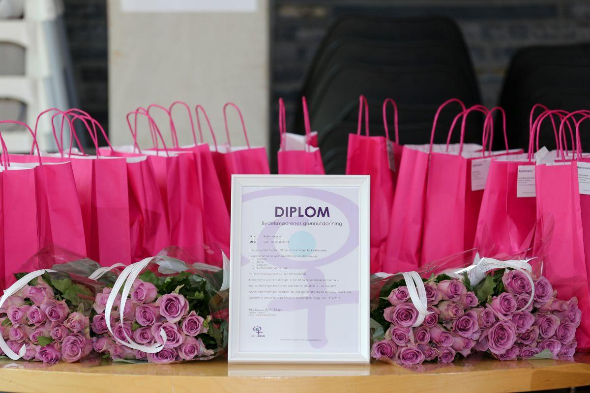 Bilde av et diplom for gjennomført Bydelsmødre-grunnutdannelse. Diplomet er rammet inn og står på et bord foran buketter med rosa roser.