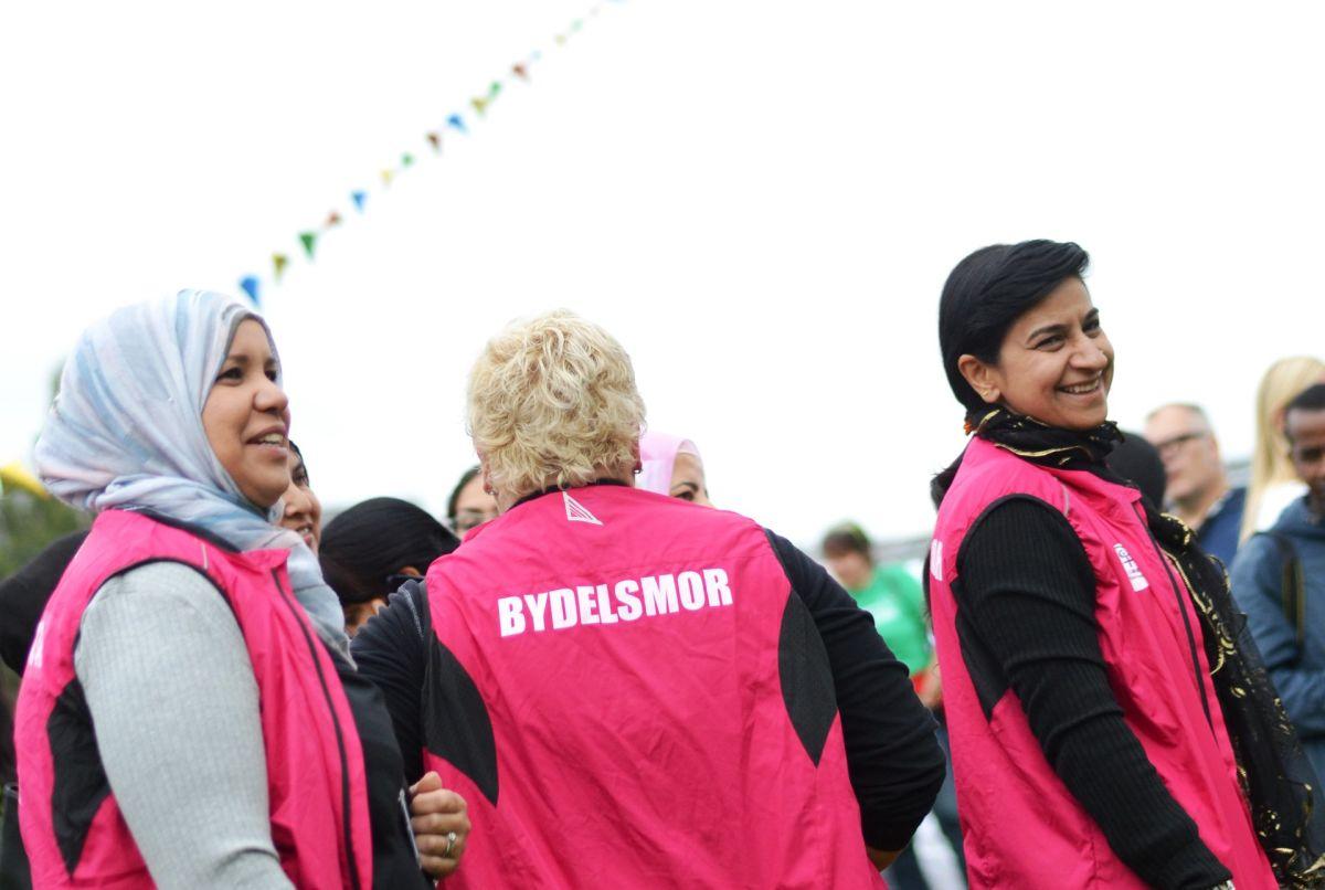 """Tre bydelsmødre i rosa vester står sammen og smiler. De er samlet på et utendørs arrangement. Vestene har påskriften """"bydelsmor"""" på ryggen."""