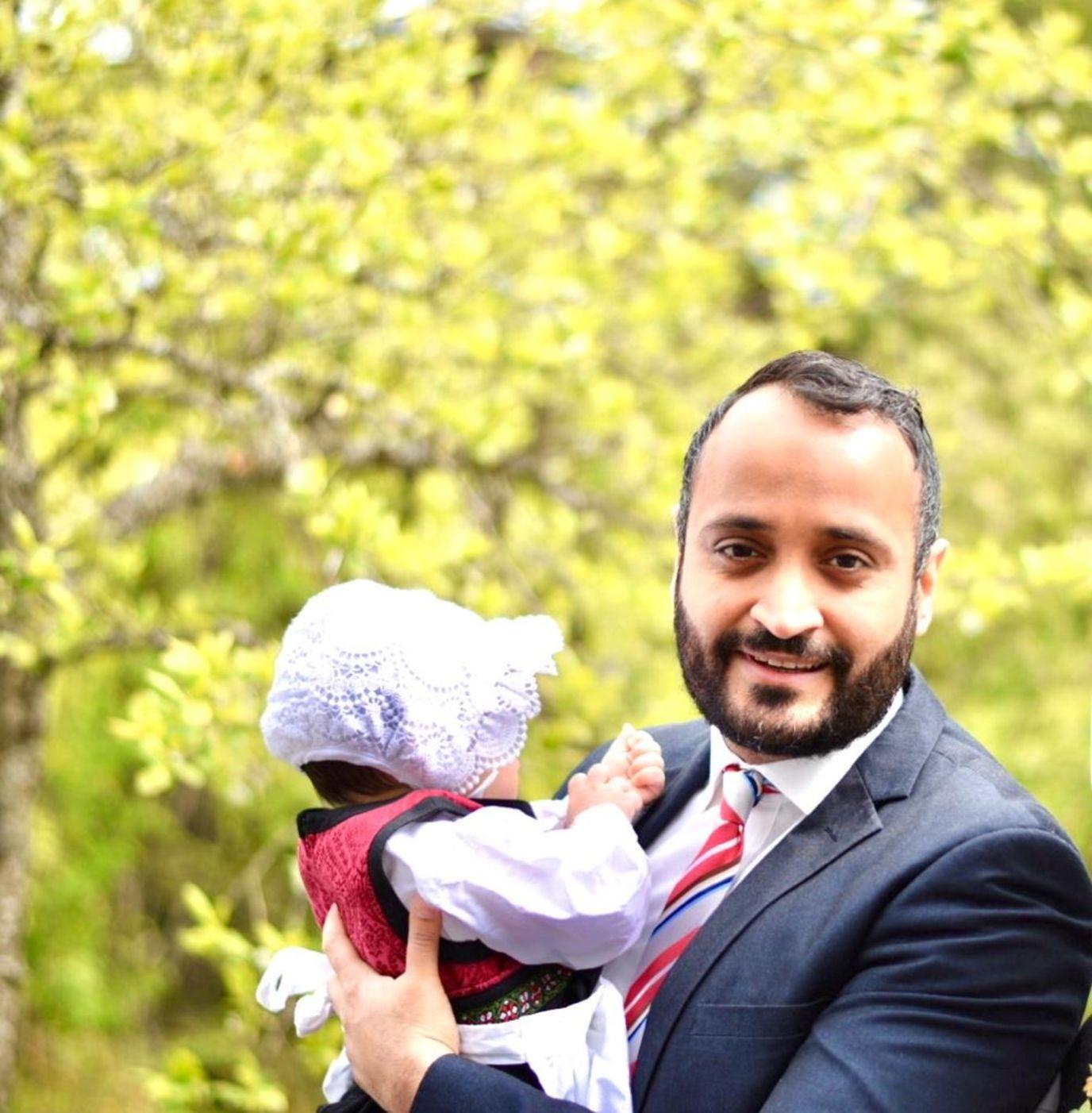 En mann kledd i dress og rødt slips står utendørs foran grønne trær. Han holder den lille datteren sin, som er kledd i bunad og kyse og har ryggen til kamera.